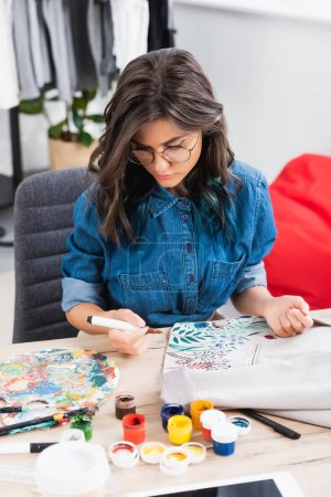 female fashion designer in eyeglasses painting on jacket at working table in clothing design studio