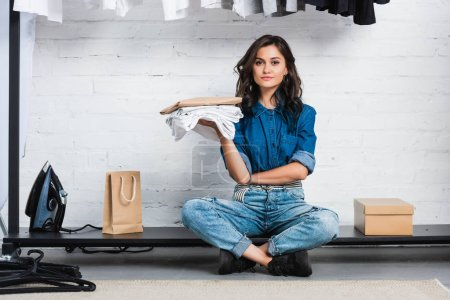 smiling female designer sitting with stack of white t-shirts and paper package in clothing design studio