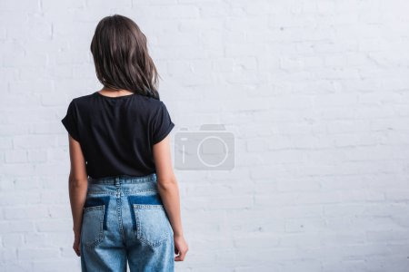 rear view of young woman in empty black t-shirt in front of brick wall