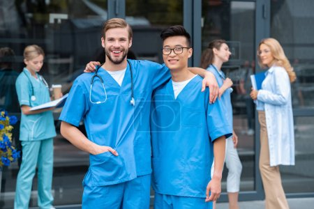 Photo for Multicultural students hugging and looking at camera near medical university - Royalty Free Image