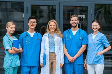 Photo for Smiling teacher and multicultural students looking at camera at medical university - Royalty Free Image