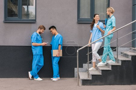 Photo for Multicultural male medical students looking at smartphone near medical university - Royalty Free Image