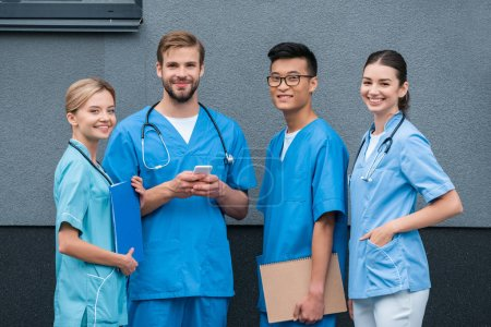 Photo for Smiling multiethnic medical students looking at camera near medical university - Royalty Free Image