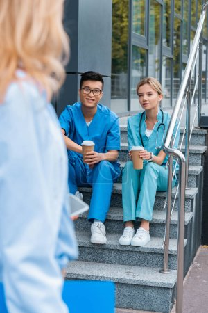 cropped image of teacher looking at medical students sitting on stairs with coffee to go