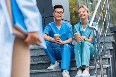 cropped image of teacher looking at smiling medical students sitting on stairs with coffee to go