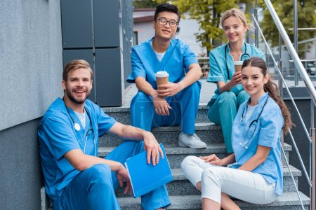 Photo for Happy multicultural medical students sitting on stairs and looking at camera - Royalty Free Image