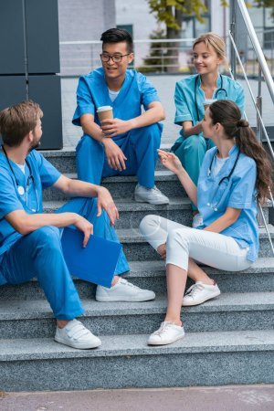 smiling multicultural medical students talking while sitting on stairs