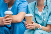 cropped image of medical students holding disposable coffee cups