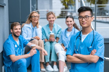 asian man standing in front of caucasian teacher and students at medical university