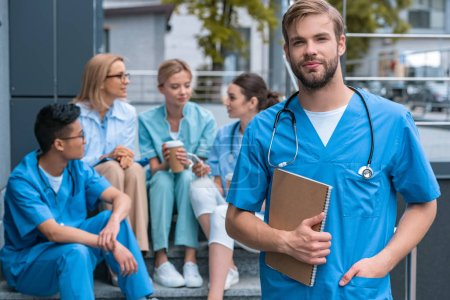 caucasian man standing in front of multiethnic teacher and students at medical university