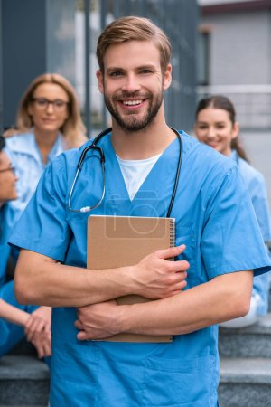 handsome caucasian medical student standing with notebook and looking at camera