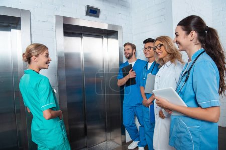 teacher with multicultural students waiting elevator at medical university