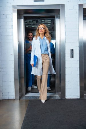 Photo for Beautiful teacher walking from elevator in medical university - Royalty Free Image