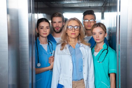 teacher and multicultural students standing in elevator at medical university