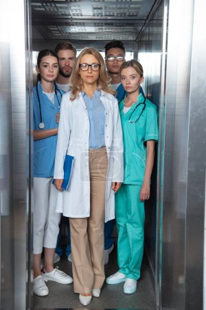 teacher and multiethnic students standing in elevator at medical university
