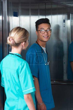 multicultural medical students entering elevator in university