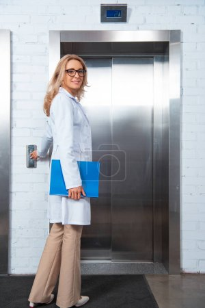 smiling attractive lecturer waiting elevator in medical university