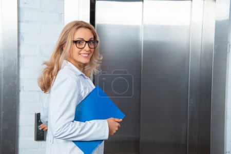 smiling attractive lecturer pressing elevator button in medical university