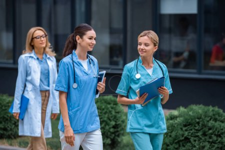 Photo for Medical students and lecturer walking on street near university - Royalty Free Image