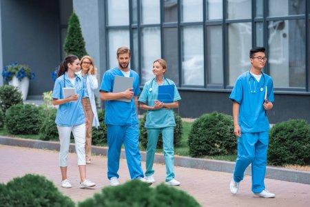 teacher and multiethnic students walking on street near medical university