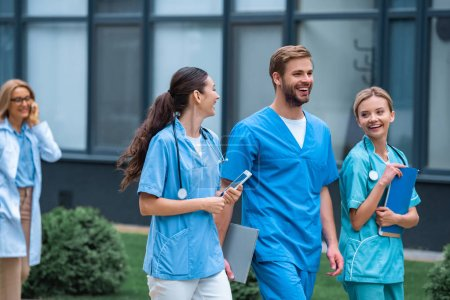 smiling medical students and lecturer walking on street near university