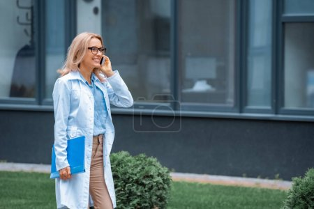 attractive teacher talking by smartphone near medical university