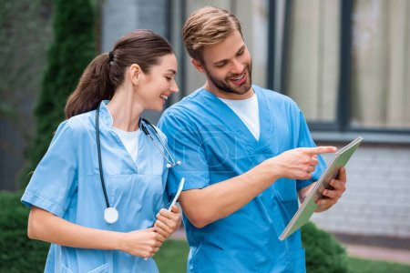 handsome medical student pointing on something in notebook to friend on street