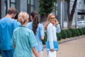 teacher talking by smartphone on street near medical university