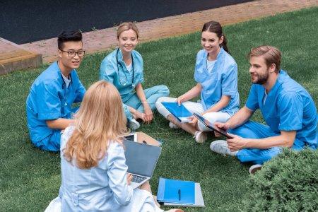 Photo pour Professeur ayant leçon avec multiculturelles étudiants à l'Université médicale sur l'herbe verte - image libre de droit