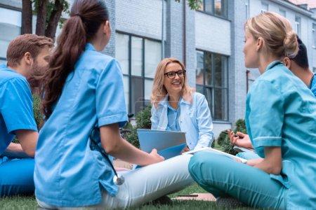 Photo pour Souriant professeur ayant cours avec des étudiants à l'Université médicale sur l'herbe verte - image libre de droit