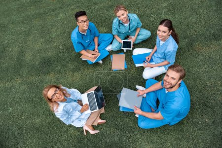 Photo for Overhead view of teacher having lesson with multicultural students at medical university on green grass - Royalty Free Image