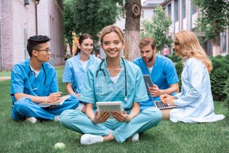 Foto de Profesor y estudiantes multiculturales al aire libre con aparatos en la Universidad médica - Imagen libre de derechos