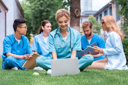 teacher and multiethnic students studying outdoors with gadgets at medical university