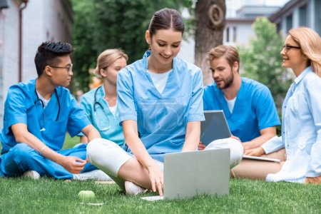 cheerful teacher and multicultural students studying outdoors with gadgets at medical university