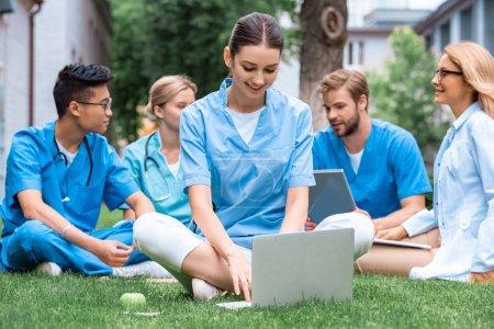 Foto de Maestro alegre y multiculturales estudiantes al aire libre con aparatos en la Universidad médica - Imagen libre de derechos