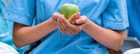 Photo pour Cropped image d'étudiant en médecine tenant une pomme verte mûre dans les mains - image libre de droit