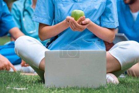 Photo for Cropped image of medical student holding ripe green apple in hands and sitting near laptop - Royalty Free Image