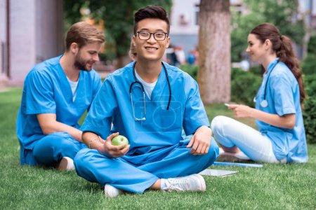 Photo pour Étudiant en médecine asiatique beau maintenant apple et regardant la caméra - image libre de droit