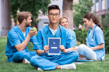 asian medical student holding tablet with loaded facebook page