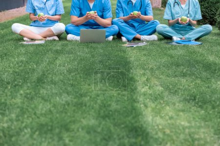 Photo for Cropped image of medical students sitting on green grass and holding apples - Royalty Free Image