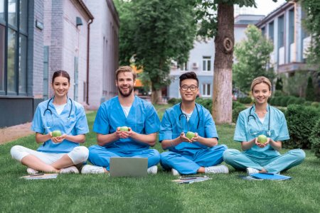 Photo for Happy multicultural medical students sitting on grass and holding apples - Royalty Free Image