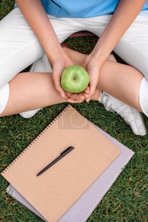 Photo pour Image recadrée de l'étudiant en médecine tenant apple en mains - image libre de droit