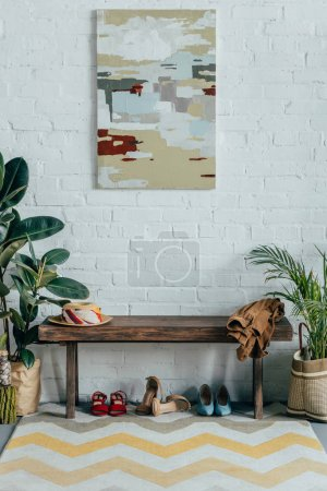 different shoes under wooden bench in corridor at home, painting on wall