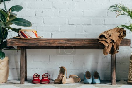 Photo pour Différentes chaussures sous un banc en bois dans le couloir à la maison - image libre de droit