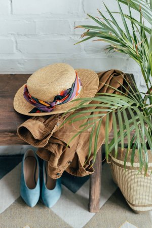 straw hat and jacket on wooden bench in corridor