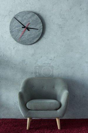 Photo pour Fauteuil gris sur tapis Bourgogne près de mur gris dans le bureau, horloge de mur - image libre de droit