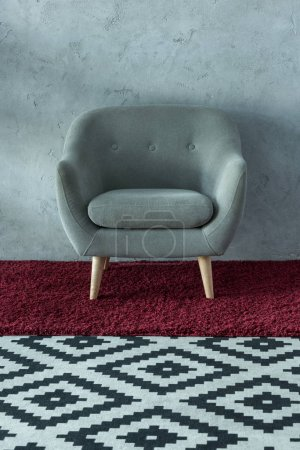 grey armchair on burgundy carpet near grey wall in office