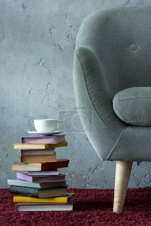 stack of books and cup of coffee on burgundy carpet near grey armchair in office