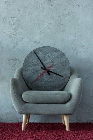 grey armchair with clock on burgundy carpet near grey wall in office