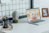 Laptop with loaded aliexpress page on table in modern office